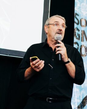 Kevin speaking at an event. He is holding a microphone and a digital control device