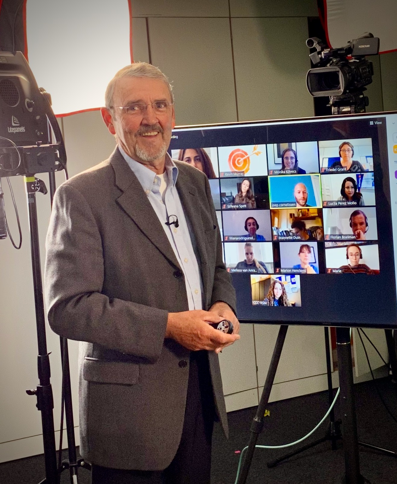 Kevin standing in front of a TV screen that is showing a video call with several people